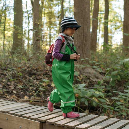 preschool girl walking in the woods